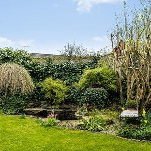 Inspiration för lantliga trädgårdar i full sol på våren, med naturstensplattor