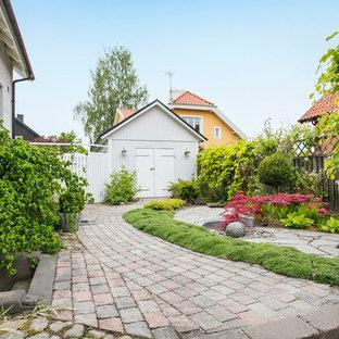 Exempel på en stor klassisk formell trädgård framför huset på våren, med en trädgårdsgång