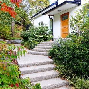 Inredning av en klassisk mellanstor formell trädgård framför huset, med en trädgårdsgång och naturstensplattor