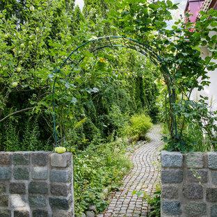 Inspiration för en mellanstor vintage formell trädgård framför huset på sommaren, med en stödmur och naturstensplattor