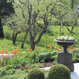 Exempel på en mellanstor klassisk trädgård i full sol på våren, med naturstensplattor