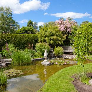 Exempel på en mellanstor klassisk trädgård på våren, med en fontän och marktäckning