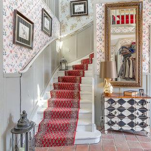 Imagen de escalera suspendida, de estilo de casa de campo, con escalones de madera, contrahuellas de madera pintada y barandilla de madera