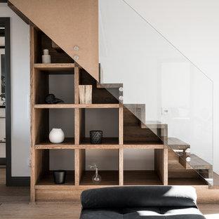 Exemple d'un escalier droit scandinave avec des marches en bois, des contremarches en bois et un garde-corps en verre.