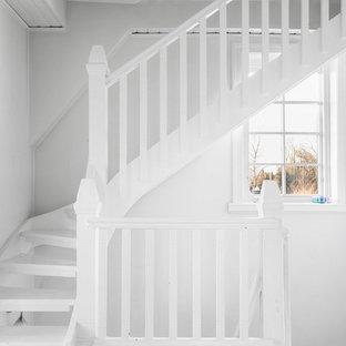 Idéer för en mellanstor lantlig svängd trappa i målat trä, med öppna sättsteg