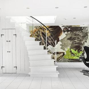 Foto di una scala curva minimalista di medie dimensioni con pedata in legno verniciato e alzata in legno verniciato
