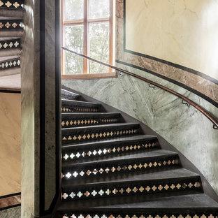 Ejemplo de escalera curva, tradicional, con escalones de metal y barandilla de madera