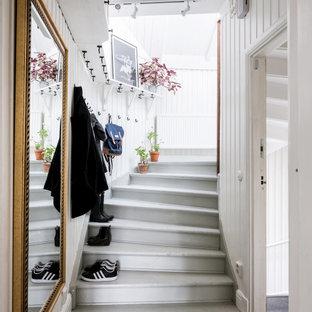 Exempel på en skandinavisk svängd trappa i målat trä, med sättsteg i målat trä