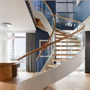 Immagine di una grande scala curva design con pedata in legno, nessuna alzata e parapetto in vetro