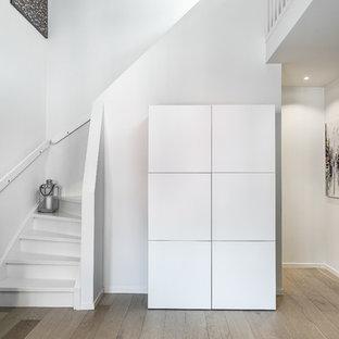 Inspiration för en minimalistisk svängd trappa i trä, med sättsteg i trä och räcke i trä