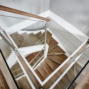 Réalisation d'un escalier nordique en U de taille moyenne avec des marches en bois, des contremarches en bois et un garde-corps en verre.