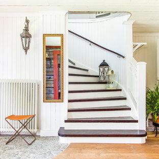 Bild på en stor minimalistisk svängd trappa i trä, med sättsteg i målat trä