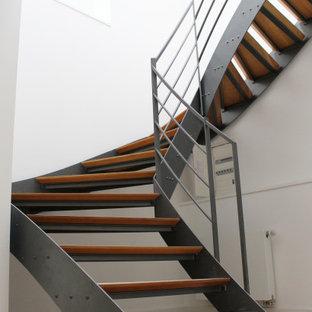 Idee per un'ampia scala curva minimal con pedata in legno e parapetto in metallo