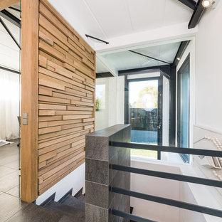 Ejemplo de escalera curva, actual, pequeña, con escalones con baldosas, contrahuellas con baldosas y/o azulejos y barandilla de metal
