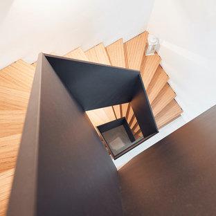 """Foto di una scala a """"U"""" industriale di medie dimensioni con pedata in legno e parapetto in legno"""
