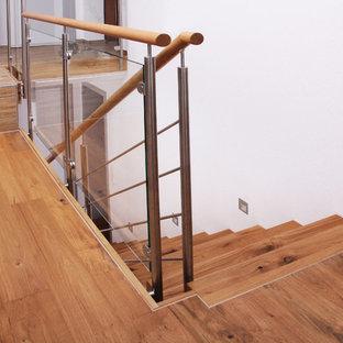 Ispirazione per una scala a rampa dritta contemporanea di medie dimensioni con pedata in legno, alzata in legno e parapetto in vetro