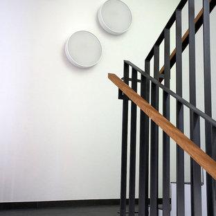 Modelo de escalera en L, tradicional, de tamaño medio, con escalones de pizarra, contrahuellas de pizarra y barandilla de metal