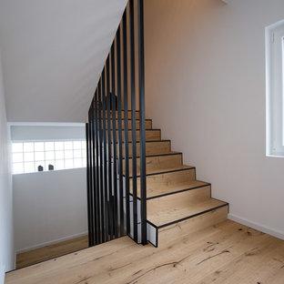 Modelo de escalera recta, rústica, de tamaño medio, con escalones de madera pintada, contrahuellas de madera pintada y barandilla de metal