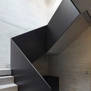Diseño de escalera en U, actual, de tamaño medio, con escalones de hormigón y contrahuellas de hormigón
