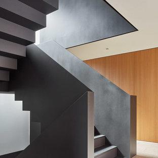 他の地域の中サイズのモダンスタイルのおしゃれな折り返し階段 (金属の手すり) の写真