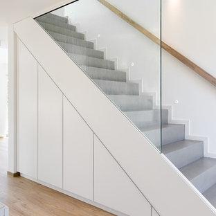 ハンブルクの中サイズのコンクリートのモダンスタイルのおしゃれな直階段 (コンクリートの蹴込み板、木材の手すり) の写真