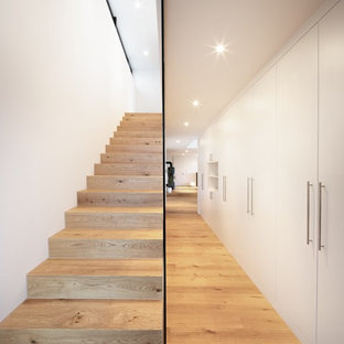 Inspiration for a mid-sized modern painted straight glass railing staircase remodel in Stuttgart with painted risers