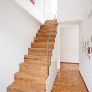 Réalisation d'un petit escalier droit nordique avec des marches en bois peint, des contremarches en bois peint et un garde-corps en métal.