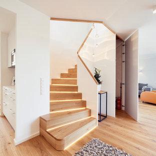 Inspiration för en liten funkis svängd trappa i trä, med sättsteg i trä och räcke i trä