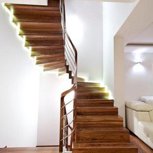 Ispirazione per una grande scala curva contemporanea con pedata in legno e alzata in legno