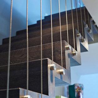 他の地域の広い木のコンテンポラリースタイルのおしゃれなサーキュラー階段 (木の蹴込み板) の写真