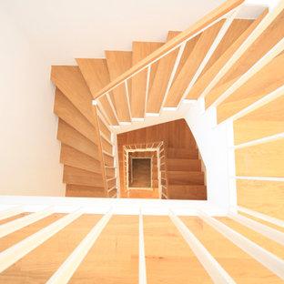 Esempio di una scala curva design di medie dimensioni con pedata in legno, alzata in cemento e parapetto in metallo