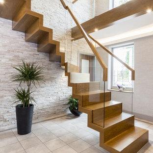 Diseño de escalera en L, contemporánea, de tamaño medio, con barandilla de vidrio, escalones de madera y contrahuellas de madera