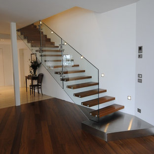 Inspiration for a mid-sized tropical painted straight open and glass railing staircase remodel in Munich