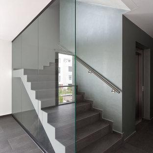Ejemplo de escalera en L, contemporánea, grande, con escalones con baldosas y contrahuellas con baldosas y/o azulejos