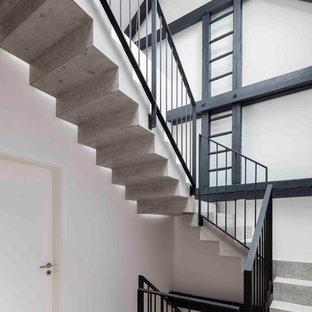 Ejemplo de escalera en U, actual, grande, con escalones de hormigón y contrahuellas de hormigón