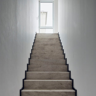ライプツィヒの巨大なトラバーチンのモダンスタイルのおしゃれな直階段 (トラバーチンの蹴込み板) の写真