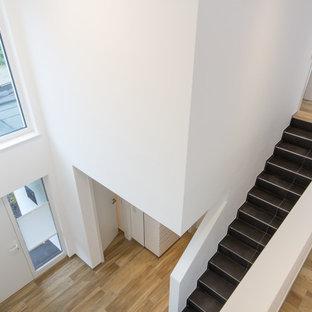 他の地域のタイルのコンテンポラリースタイルのおしゃれな直階段 (フローリングの蹴込み板、金属の手すり) の写真