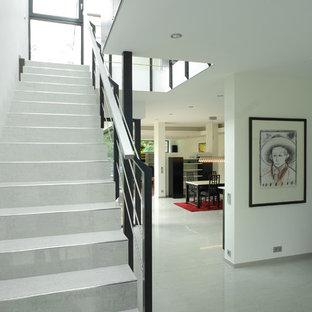 Foto de escalera suspendida, minimalista, de tamaño medio, con escalones con baldosas, contrahuellas con baldosas y/o azulejos y barandilla de metal
