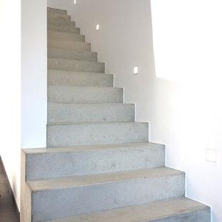 Immagine di una scala a rampa dritta design di medie dimensioni con pedata in cemento e alzata in cemento