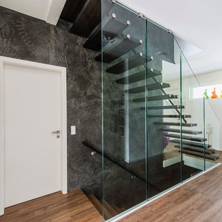 Mid-sized trendy painted straight open and glass railing staircase photo in Hamburg