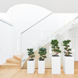 Große, Gewendelte Moderne Holztreppe mit Holz-Setzstufen und Glasgeländer in Stuttgart