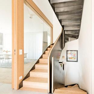 Große Moderne Holztreppe in U-Form mit Holz-Setzstufen und Stahlgeländer in München