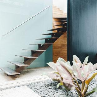 Imagen de escalera recta, minimalista, pequeña, sin contrahuella, con escalones de metal y barandilla de metal