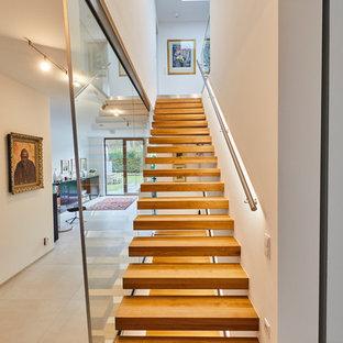 Gerade, Große Moderne Treppe mit gebeizten Holz-Treppenstufen, offenen Setzstufen und Stahlgeländer in Dortmund