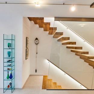 Imagen de escalera suspendida, contemporánea, de tamaño medio, con escalones de madera pintada y barandilla de metal