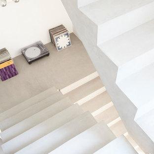 Ispirazione per una scala sospesa moderna di medie dimensioni con pedata in cemento, alzata in cemento e parapetto in vetro