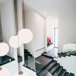 Gerade, Große Moderne Treppe mit gefliesten Treppenstufen, gefliesten Setzstufen und Glasgeländer in Düsseldorf