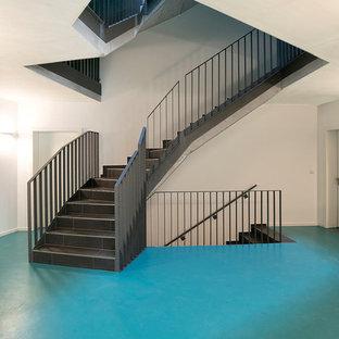 Diseño de escalera en U, contemporánea, grande, con escalones de pizarra, contrahuellas de pizarra y barandilla de metal