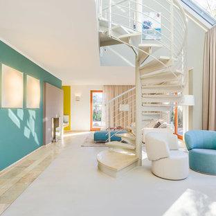 Réalisation d'un grand escalier sans contremarche hélicoïdal design avec des marches en marbre et un garde-corps en métal.