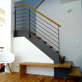 Exempel på en mellanstor modern u-trappa i trä, med sättsteg i metall